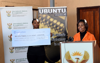 Minister Maite Nkoana-Mashabane hands over a cheque to a representative of the Nelson Mandela Trust during the 67 minutes of Mandela Day, Winterveldt, Pretoria, South Africa, 17 July 2015.